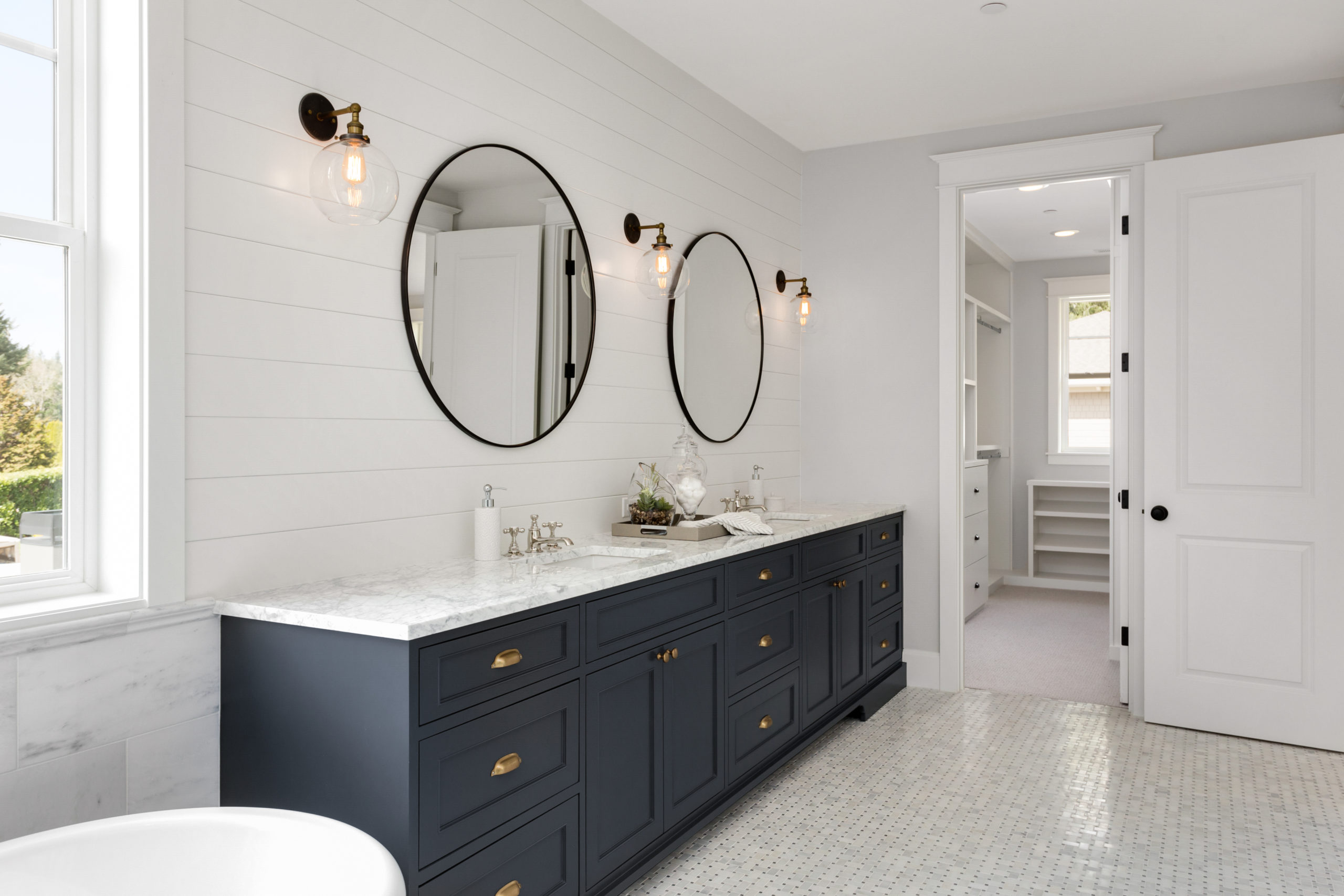 remodel contractors renovate Bathroom in New Luxury Home with Two Sinks and Dark Blue Cabinets. Shows Walk-In Closet
