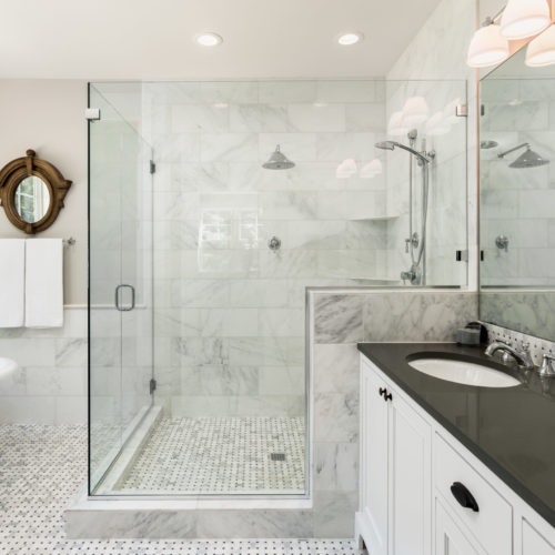 remodel contractors renovate a Beautiful master bathroom with shower, bathtub, and sink, with high end furnishings, lights on